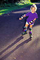 Young girl wearing protective gear rollerblading on roadway