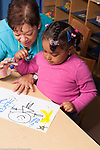 Education preschool 3-4 year olds art activity female teacher talking to girl about her drawing