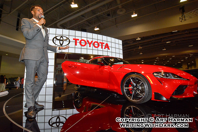 Demonstrating Toyota model at auto show.