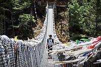 A woman trekker crossing a hanging bridge in Nepal's Khumbu Valley