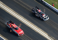 Apr. 28, 2012; Baytown, TX, USA: Aerial view of NHRA funny car driver Courtney Force (right) races alongside Johnny Gray during qualifying for the Spring Nationals at Royal Purple Raceway. Mandatory Credit: Mark J. Rebilas-