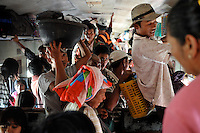 Passengers pack into the common class compartment of  the Mandalay to Rangoon train , Burma Nov 2008.  <br />