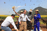 Covered in bees, Mister Yang Chuan tries to smile to the gathered crowd while the anchormen from CCTV4 continue the program with a lot of courage.