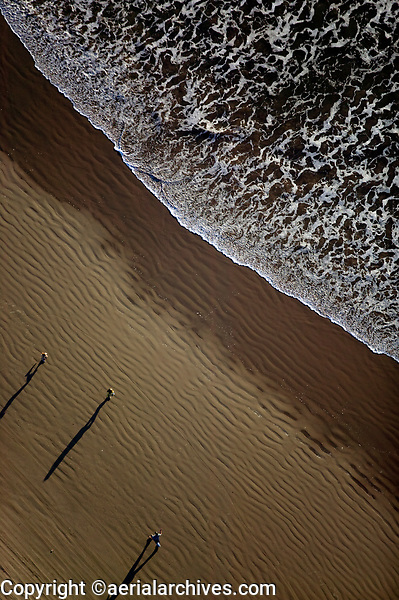 aerial photograph of people walking on a California beach in the late afternoon