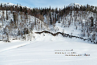 Allen Moore runs past resting teams Jason and Lance Mackey on the Skwentna River  between the Finger Lake and Rainy Pass checkpoint during Iditarod 2016.  Alaska.  March 07, 2016.  <br /> <br /> Photo by Jeff Schultz (C) 2016 ALL RIGHTS RESERVED