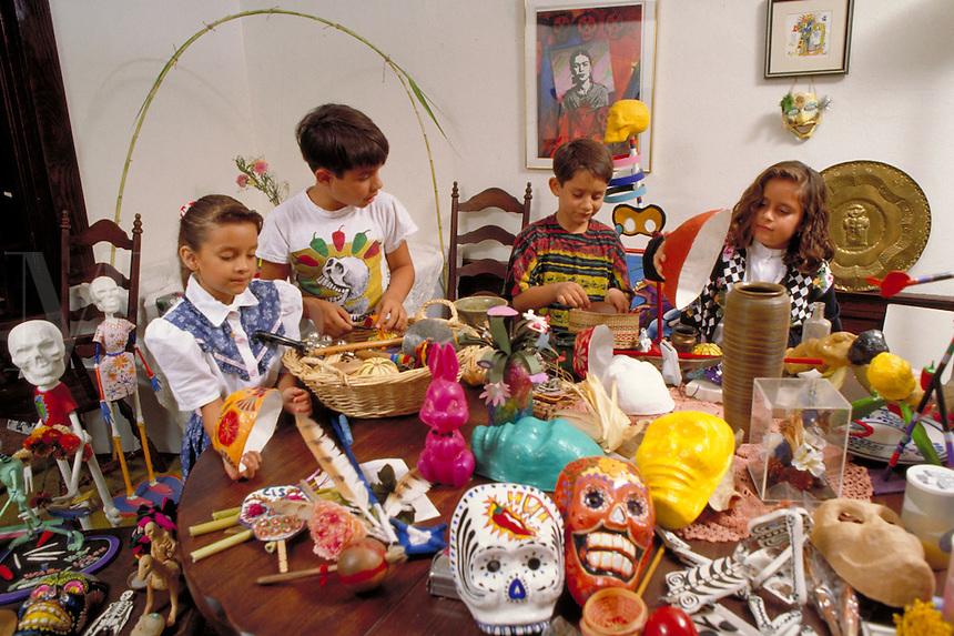 HISPANIC CHILDREN AT HOME PREPARING ALTAR FOR DAY OF THE DEAD CELEBRATION. HISPANIC FAMILY. SACRAMENTO CALIFORNIA.