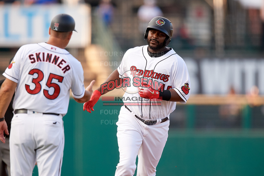 Rochester Red Wings designated hitter Chris Carter (45) is congratulated by manager Joel Skinner (35) as he rounds third base after hitting a home run in the bottom of the second inning during a game against the Lehigh Valley IronPigs on June 30, 2018 at Frontier Field in Rochester, New York.  Lehigh Valley defeated Rochester 6-2.  (Mike Janes/Four Seam Images)