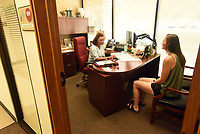 Jacki Gustin (left), human resources administrative assistants, talks with newly hired math teacher Brielle Myers on Wednesday July 14 2021 at the Rogers school administration building.<br />(NWA Democrat-Gazette/Flip Putthoff)