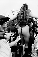 """Switzerland. Zürich. A sexy woman, wearing a tight underwear, sexy stockings, high-heeled boots, dances during the Street Parade which is a yearly techno event in Zurich.  A young man shows up his middle finger ( fuck off) to the woman's bottom. In Western culture, the finger or the middle finger (as in giving someone the (middle) finger, is an obscene hand gesture. The gesture communicates moderate to extreme contempt, and is roughly equivalent in meaning to """"fuck off"""", """"fuck you,"""" """"shove it up your ass / arse,"""" """"up yours,"""" or """"go fuck yourself."""" It is performed by showing the back of a hand that has only the middle finger extended upwards. The Street Parade is the most attended techno parade in the world and is the largest annual event in Zurich. Officially a demonstration for freedom, love and tolerance attended by up to a one million people, it proceeds along the side of Lake Zurich on the second Saturday of August. © 1995 Didier Ruef"""