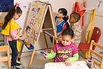 Education preschool 4 year olds art activity girls painting at easel, girl n foreground drawing and writing boy observing the painting activity horizontal