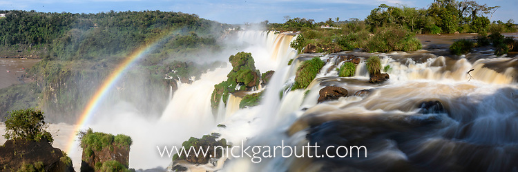 Rainbow at Iguasu Falls (also Iguazu Falls, Iguazú Falls, Iguassu Falls or Iguaçu Falls) on the Iguasu River, Brazil / Argentina border. Photographed from the Argentinian side of the Falls. Argentina.