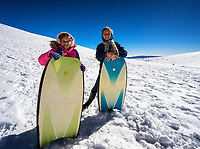 Young girls on a snow-covered Mauna Kea sled with their boogie boards on a sunny Big Island day.