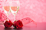 Glasses of champagne and red roses