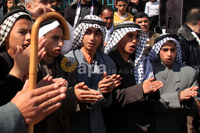 A Palestinian farmers celebrate after planting olive trees during a protest against the uprooting of trees belonging to Palestinians by Jewish settlers near the settlement of Elon Moreh in the West Bank village of Deir al-Hatab, Monday, Feb. 28, 2011. Photo by Wagdi Eshtayah