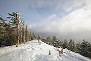 Windy conditions cause snow and clouds to blow across the white Mountains from Mount Tecumseh in Waterville Valley, New Hampshire during the winter months.