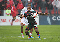 Toronto, Ontario - May 3, 2014: Toronto FC forward Jermain Defoe #18 and New England Revolution defender Andrew Farrell #2 in action during a game between the New England Revolution and Toronto FC at BMO Field.<br /> The New England Revolution won 2-1.
