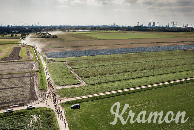 """Peloton riding the dusty gravel roads. <br /> <br /> Antwerp Port Epic 2018 (formerly """"Schaal Sels"""")<br /> One Day Race: Antwerp > Antwerp (207km of which 32km are cobbles & 30km is gravel/off-road!)"""