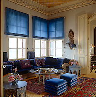 Soft velvet cushions and pouffes in a bold shade of blue furnish this formal sitting room