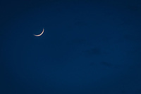 A sliver of moon and hints of clouds on a spring night.