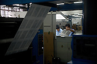 """Press technicians check the quality of Bible pages as they come off a new printing press in the Amity Printing Company's new printing facility in Nanjing, China....On May 18, 2008, the Amity Printing Company in Nanjing, Jiangsu Province, China, inaugurated its new printing facility in southern Nanjing.  The facility doubles the printing capacity of the company, now up to 12 million Bibles produced in a year, making Amity Printing Company the largest producer of Bibles in the world.  The company, in cooperation with the international organization the United Bible Societies, produces Bibles for both domestic Chinese use and international distribution.  The company's Bibles are printed in Chinese and many other languages.  Within China, the Bibles are distributed both to registered and unregistered Christians who worship in illegal """"house churches."""""""