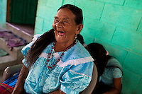 """An old Salvadoran woman laughs, while watching the procession of the Flower & Palm Festival in Panchimalco, El Salvador, 8 May 2011. On the first Sunday of May, the small town of Panchimalco, lying close to San Salvador, celebrates its two patron saints with a spectacular festivity, known as """"Fiesta de las Flores y Palmas"""". The origin of this event comes from pre-Columbian Maya culture and used to commemorate the start of the rainy season. Women strip the palm branches and skewer flower blooms on them to create large colorful decoration. In the afternoon procession, lead by a male dance group performing a religious dance-drama inspired by the Spanish Reconquest, large altars adorned with flowers are slowly carried by women, dressed in typical costumes, through the steep streets of the town."""