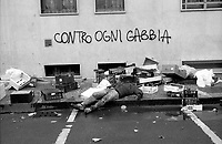 "Milano, quartiere Bovisa, periferia nord. Un uomo ubriaco sdraiato tra cassette vuote di frutta e verdura al mercato rionale e la scritta sul muro ""contro ogni gabbia"" --- Milan, Bovisa district, north periphery. A drunk man lying among empty boxes of fruit and vegetables at the local market and the writing on the wall ""against every cage"""