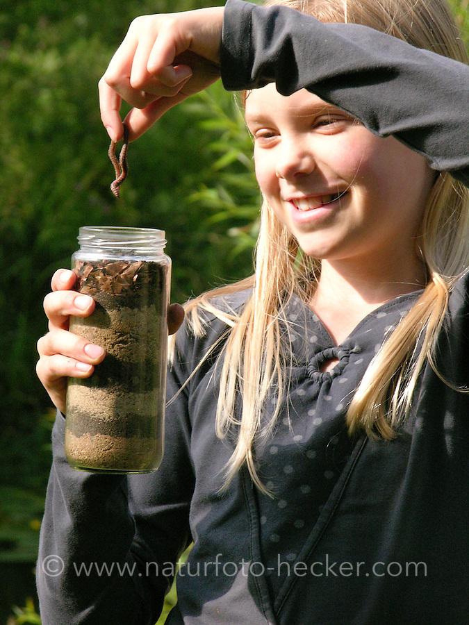 Mädchen, Kind mit Regenwurm, Tauwurm, legt den Regenwurm in ein mit Erdschichten, Erde gefülltes Glas, Experiment wird zeigen, dass der Wurm die Erschichten durchmischt, Lumbricus spec., common earthworm, earthworm, lob worm, dew worm,
