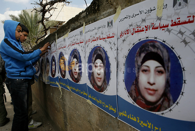 Relatives of Palestinian detainee, Hana Shalabi, stick up placards depicting Shalabi, in the West Bank village of Birqin, near Jenin February 27, 2012. Shalabi, released by Israel in a prisoner swap last year but re-arrested earlier this month and held without charge, is on a hunger strike to protest at her treatment, officials said on Monday.  Photo by Wagdi Eshtayah
