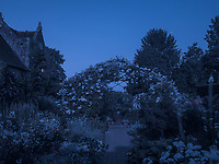 The rose arbour in the 'white garden' is bathed in the soft light of a rising moon