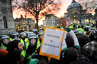 As police and protestors clash, one protestor holds up a poster reading 'Education is Progression' during a student demonstration in Westminster, central London on the day the government passed a bill to increase university tuition fees.