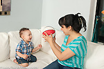 12 month old baby boy with mother playing with toy ball
