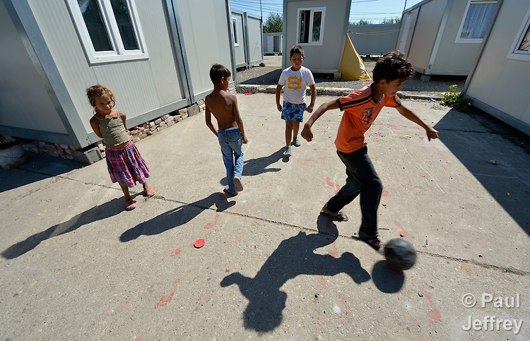 Roma children play football amid shipping containers that have been converted into houses in Makis, a village outside of Belgrade, Serbia. These Roma families were evicted from an urban squatter settlement in 2012 to make way for construction of new apartments and office buildings. The shipping containers they now call home, which were provided at no cost by local authorities, are far from the city center.