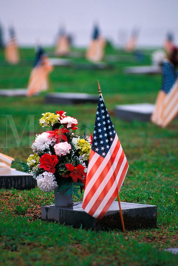 Flag and flowers by Veteran marker.