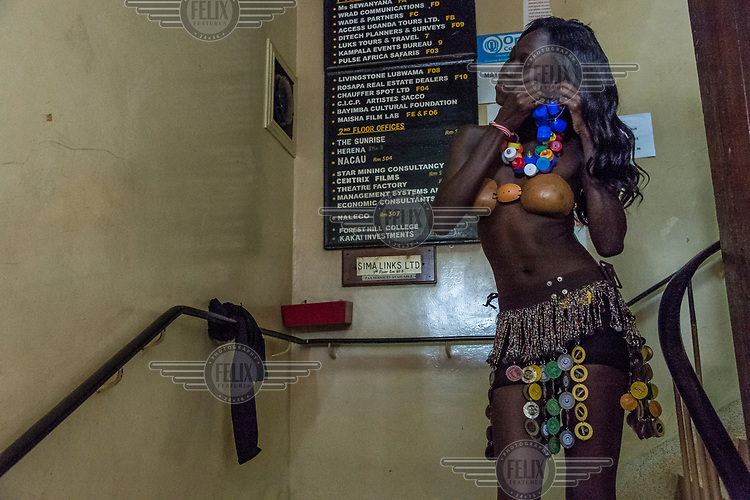 Backstage at the Trash on Fashion Show, at the Kampala National Theatre, a model puts on jewellery made from plastic bottle tops and crushed metal bottle caps. The clothes presented during the show were created by the artist collective Afrika Arts Kollective, which specialises in waste recovery and recycling. Their goal is to make the public aware of the possibilities of economy and ecology which conceal everyday life and its waste.