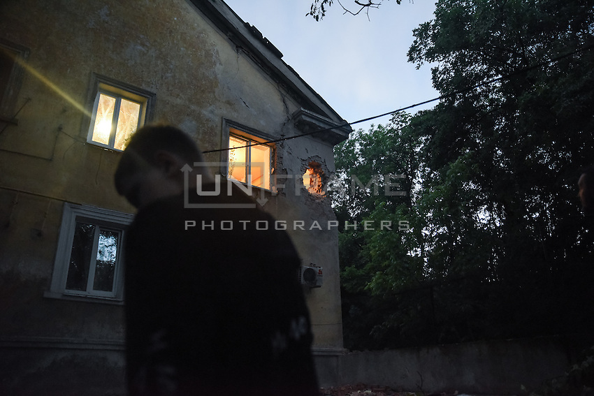 A boy near a civil building after heavy shelling in Donetsk, 1 June 2015