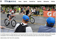An athlete waves to cheering vans in Verona during IRONMAN Wisconsin on Sunday, Sep. 12, 2021 | Wisconsin State Journal article front page A1 and A6 on Monday, Sep. 13, 2021 and online at https://madison.com/wsj/news/local/watch-now-return-of-ironman-triathlon-brings-exhilarating-atmosphere-to-madison/article_b1f39604-d312-5d4a-b0d8-c85bfbfab933.html