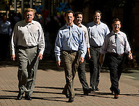 A group of business men dressed in causal attire walk in uptown Charlotte, NC.