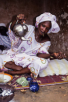 Agnibilikrou, Ivory Coast, Cote d'Ivoire.  Woman Pouring Tea, Toothpick in her Mouth.