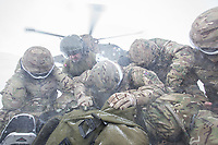 Troops huddle together over their kit as a Merlin helicopter takes off during practice in the Arctic, in the mountains near Bardufoss, Norway. <br /> <br /> In 2019 the Arctic exercise Clockwork passed 50 years of training in Norway, and now has a permanent base within the Norwegian Air Force base at Bardufoss. <br /> <br /> 845 Naval Air Squadron is a squadron of the Royal Navy's Fleet Air Arm. Part of the Commando Helicopter Force, it is a specialist amphibious unit operating the Leonardo Commando Merlin Mk3 helicopter and provides troop transport and load lifting support to 3 Commando Brigade Royal Marines.<br /> <br /> ©Fredrik Naumann/Felix Features