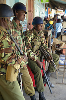 Kenya. Rift Valley province. Nakuru. 25.01.2008. Kikuyus policemen stand near a shop and control the streets during the inter-ethnic strifes The three men wear military outfitts, a blue helmet on the heads and carry weapons. The Kikuyus are Kenya's most populous ethnic group. © 2008 Didier Ruef