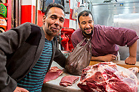 Fes, Morocco.  Moroccan Butcher and his Customer, Talaa Kebira Street in the Old City.
