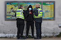 Pictured: Two police officers speak with a young man in Swansea Bay. Friday 16 April 2021<br /> Re: People enjoy an evening out after Covid-19 lockdown rules were relaxed, in Swansea Bay, Wales, UK.