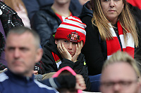 SUNDERLAND, ENGLAND - MAY 13: A young Sunderland fan holds his head in disappointment during the Premier League match between Sunderland and Swansea City at the Stadium of Light, Sunderland, England, UK. Saturday 13 May 2017