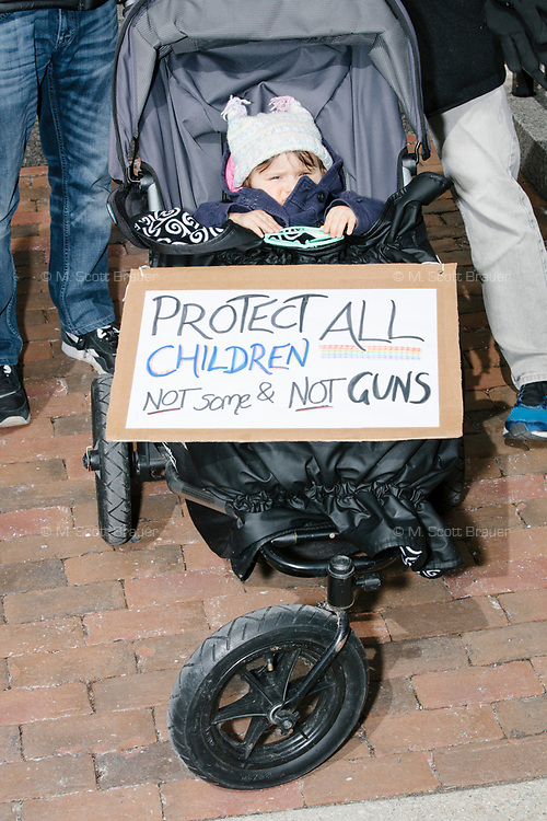 """A sign on a baby stroller reads """"Protect all children / Not some & not guns"""" as people take part in the March For Our Lives protest, walking from Roxbury Crossing to Boston Common, in Boston, Massachusetts, USA, on Sat., March 24, 2018, in response to recent school gun violence."""