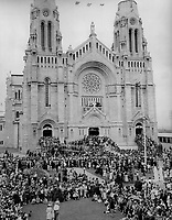 Unfinished Basilica of Ste. Anne de Beaupre; Que.; seen here; was visited Saturday by tens of thousands from all over the continent. It was the feast of the shrine a patron. Ste. Anne; the mother of Mary; who was the mother of Jesus. Crowds await the ceremonies of blessing of the sick. Note the ramp for wheel chairs.<br /> <br /> [unknown]<br /> Picture, 1947<br /> <br /> PHOTO : Toronto Star Archives - AQP