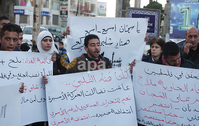 """Palestinians hold up banners for Hana Al-Shalabi, a Palestinian prisoner on hunger strike jailed in Israel, as they protest against Israel's policy of administrative detention, in the West Bank city of Ramallah , Monday, Feb. 27, 2012. Last week, Islamic Jihad member Khader Adnan drew international attention to the controversial Israeli policy of holding suspected Palestinian militants without charge, as he agreed to end his 66-day hunger strike to protest his imprisonment without charge after reaching a deal with Israel that will free him in April. Arabic text on poster reads: """"Down with the policy of administrative detention"""", top, and """" Release the prisoner Hana Al-Shalabi"""". Photo by Issam Rimawi"""
