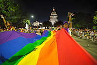 AUSTIN, TEXAS - 2016 Austin PRIDE Parade makes it way through downtown as marchers hold the rainbow flag with Texas State Capitol background on Saturday, Aug. 27, 2016. <br />
