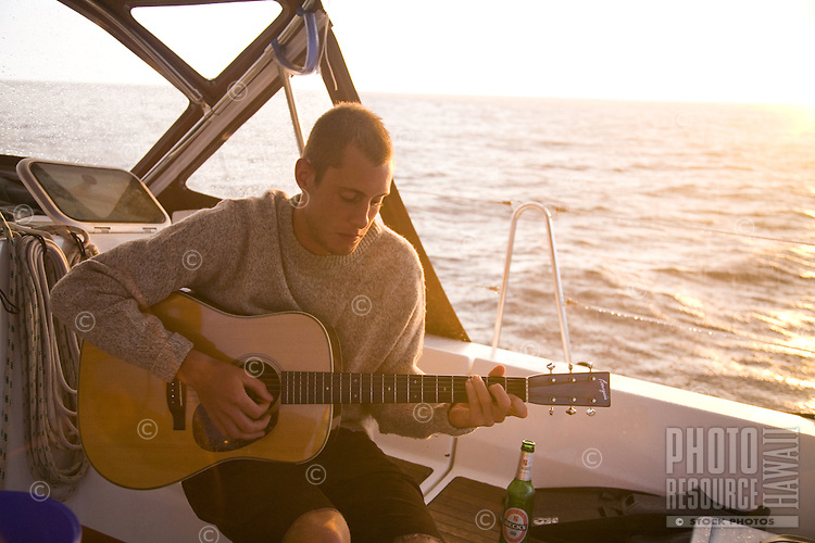 Young man playing guitar on a sailboat at sunset