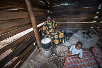 Uganda, Butema. Milly Mugisa (53), uses a Biolite stove at her home, it charges a light and charges her mobile phone. Cooking at home with her baby.