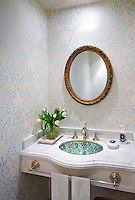 Delicate blue and white floral pattern wallpaper and a marble washstand give the bathroom a traditional feel.